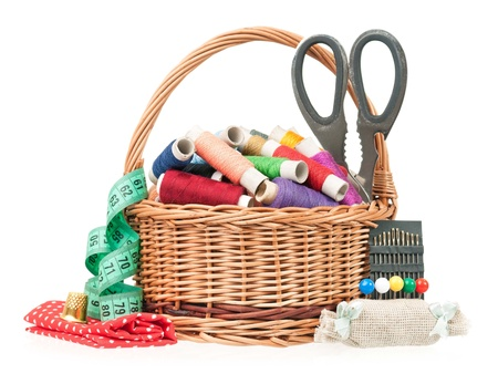 Colorful threads in a wicker basket with sewing accessories on white background