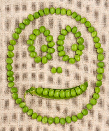 Smiling face from beans of green peas on a burlap photo