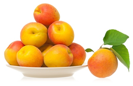 Heap of ripe yellow apricots on a plate isolated on white background photo