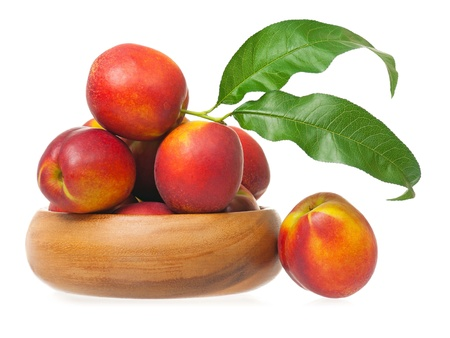 Red nectarines on a bamboo bowl isolated on white background photo