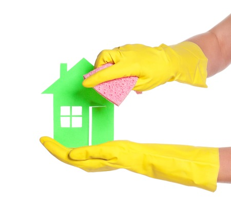Paper house on woman hands in gloves over white background photo