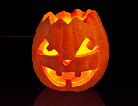 hollows: Illuminated hallowenn pumpkin with a candle over black background Stock Photo