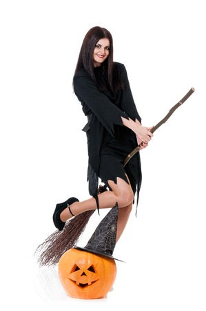 Young sexy witch flying on a broom isolated on white background cutout photo