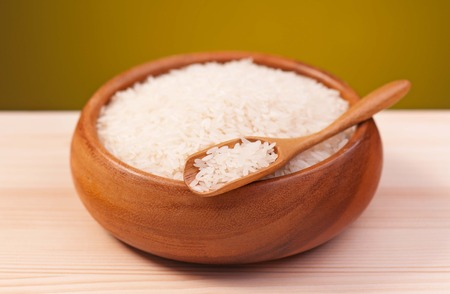 White rice in a bamboo bowl on a wooden surface over dark background