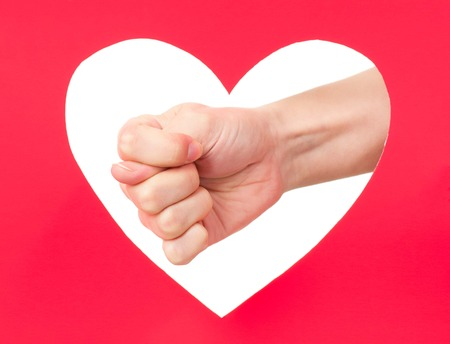Woman hand shows fig gesture against red paper heart photo