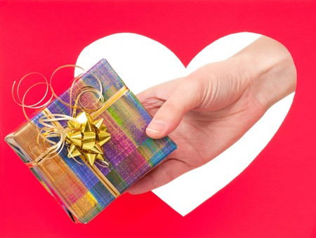 Woman hand give a gift box against red heart concept photo