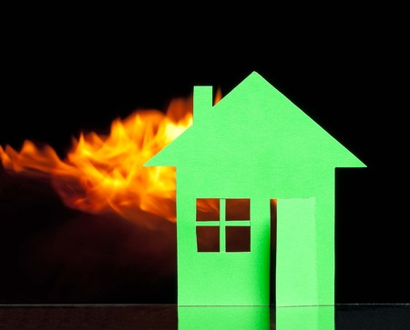 Paper house in a fire over black background