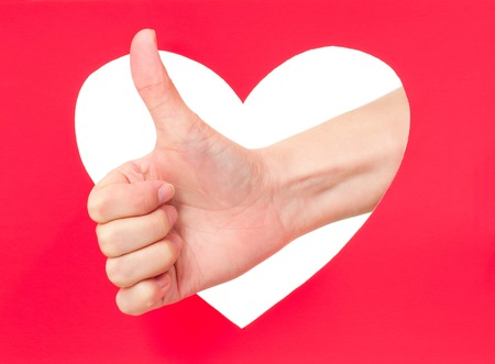 Woman hand shows okay gesture against red heart photo