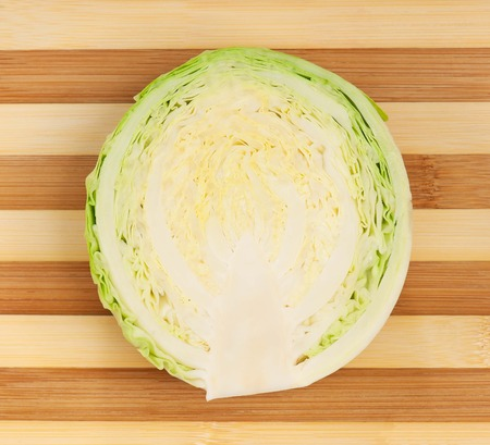 Half of fresh cabbage on a wooden chopping board close-up photo