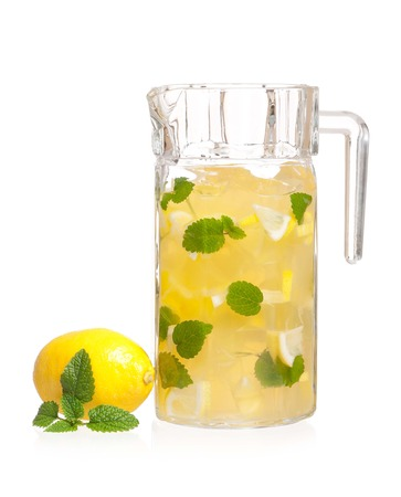 Pitcher of lemonade with lemon and mint isolated on white background