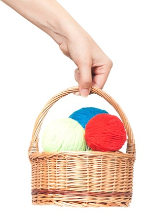 Threads for knitting in a wicker basket in woman hand over white background photo