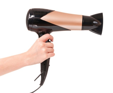 Hair dryer in a woman hand isolated on white background photo
