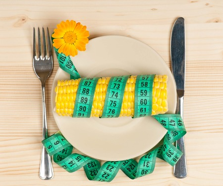 Sweetcorn with tape measure and cutlery over wooden surface photo