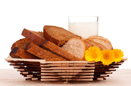 crackling: Slices of bread for sandwich on a decorative dish with glass of milk over white background