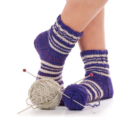 Warm socks on a female legs with threads and spokes over white background