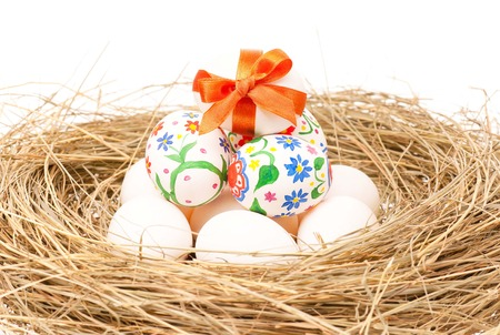 Raw and decorated eggs in a birds nest over white background photo