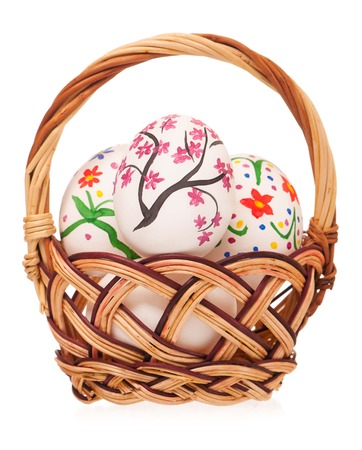 Colorful Easter eggs in a wicker basket isolated on white background photo