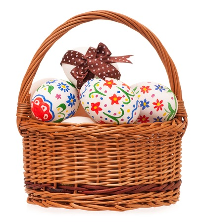 Colorful Easter eggs in a wicker basket isolated on white background Stock Photo