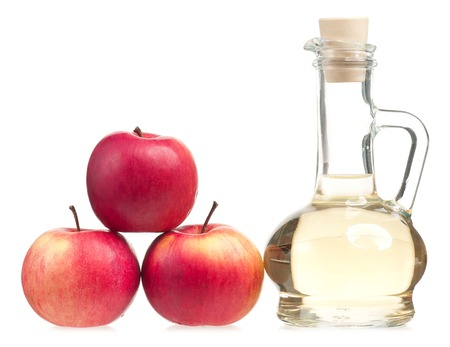 Apple vinegar in the glass bottle with fresh apples isolated on white