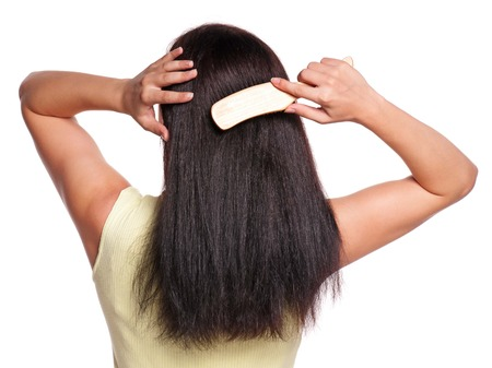 Picture of the back of a woman with long hair with hairbrush on white