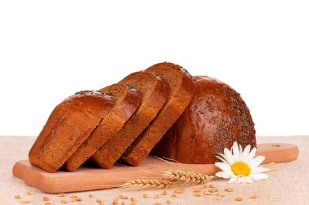 Newly-baked rye bread on the cutting board over white background