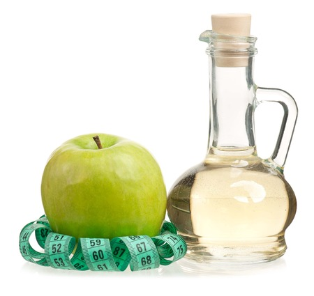 Apple vinegar in the glass bottle with fresh apples isolated on white background