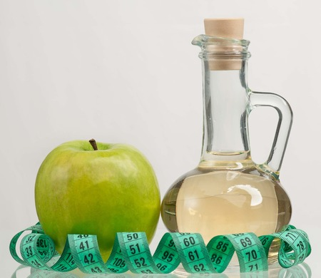 Apple vinegar in the glass bottle with fresh apples on a grey background