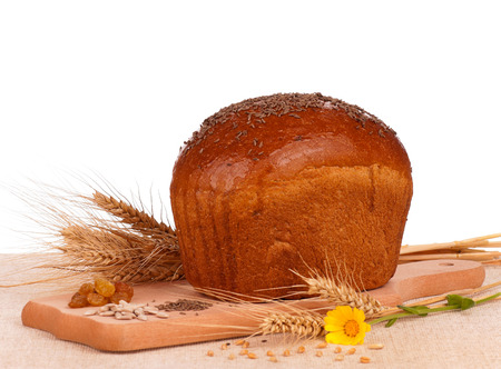 Whole rye bread on a cutting board over white background photo