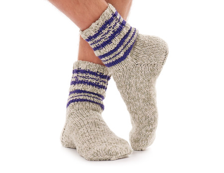 Legs of caucasian man in knitted warm socks over white background