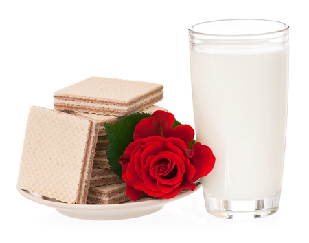 Milk with wafers and red rose for a romantic breakfast over white background