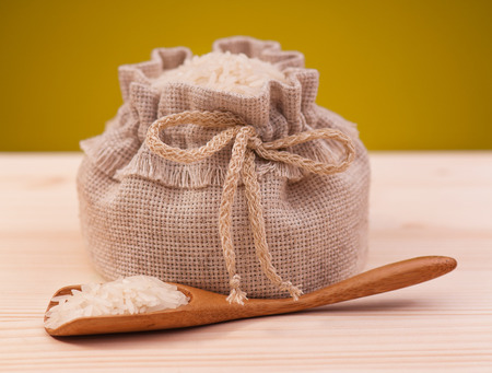 Uncooked rice in a sack over dark yellow background close-up photo
