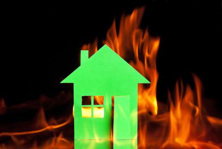 incendio casa: Casa de papel abrazó con una llama sobre fondo negro concepto