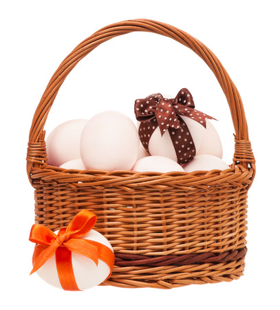 Raw eggs in a wicker basket isolated on white background photo