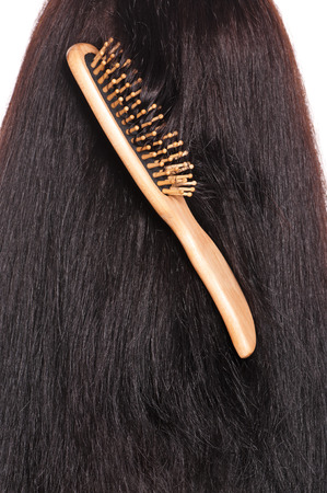 Wooden hairbrush got confused in hair over white photo