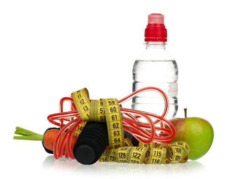 Skipping rope with a tape measure and fresh healthy food on white background Stock Photo