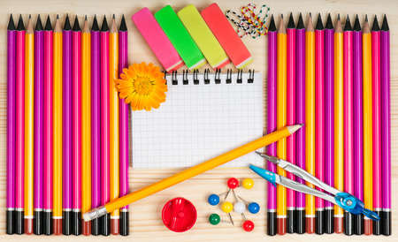 Colorful pencils with notepad and school accessories over wooden surface photo