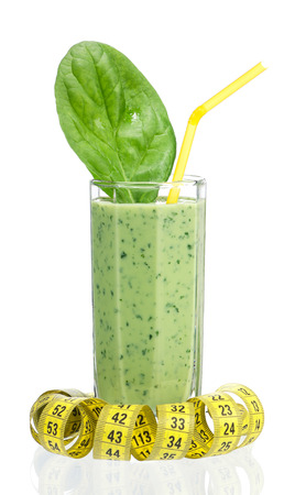 tubule: A glass of spinach smoothie with tubule and tape measure over white Stock Photo