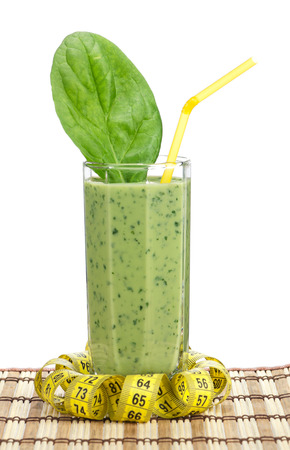 tubule: A glass of spinach smoothie with tubule and tape measure over white background Stock Photo