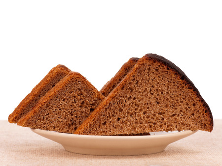 Slices of rye bread for sandwich on a plate over white photo