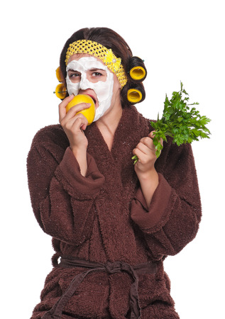 Beautiful young woman with a mask on her face eats apple isolated over white photo