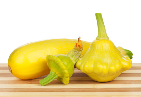 cymbling: Fresh yellow zucchini fruits and vegetable marrows on white background Stock Photo