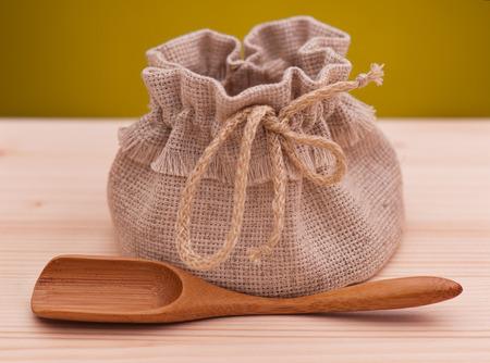sacco juta: sacco di iuta con cucchiaio di legno su una superficie di legno su sfondo giallo scuro Archivio Fotografico