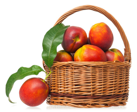 Tasty nectarines in a wicker basket isolated on white background photo