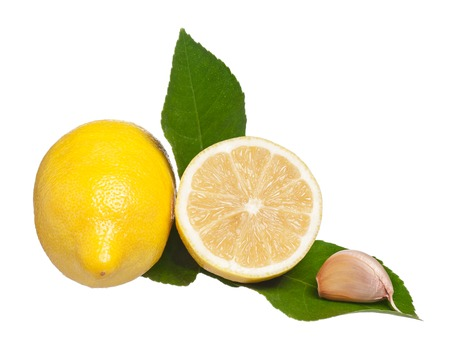 clean artery: Yellow lemon with green leaves and raw garlic isolated on a white background