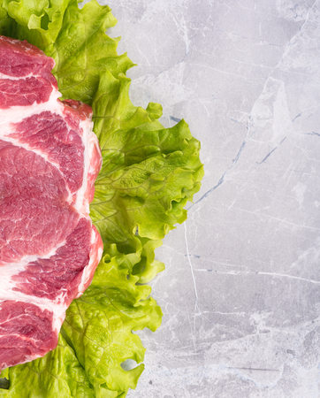 tabletop: Fresh raw pork on green lettuce leaves over table-top background Stock Photo