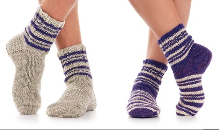 knitting: Pair of man and woman in the knitted socks over white background Stock Photo