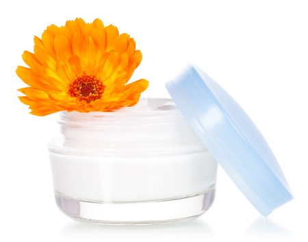 liniment: Closeup of jar of moisturizing face cream and fresh marigold flower isolated on white background