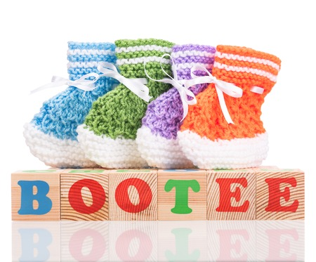 hank: Bright cute little bootee with playing cubes isolated over white background Stock Photo