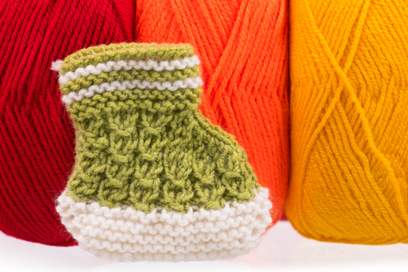 Cute little bootee over bright acrylic yarn background Stock Photo