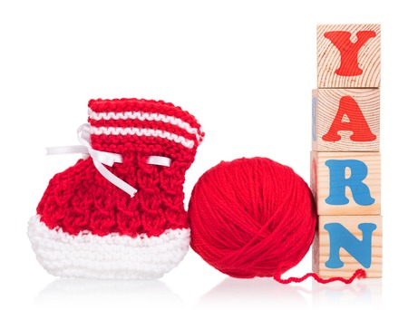 woollen: Bright little bootee with playing cubes isolated over white background Stock Photo